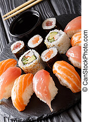 Set of sushi with salmon and tuna, California rolls, maki, soy sauce closeup on a black slate board. vertical