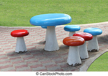 Set of table and chairs on pathway of public lawn