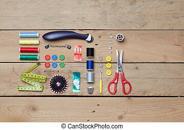 Set of tailoring tools on wooden background