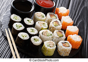 set of tasty Japanese rolls closeup with sauces on a stone. horizontal