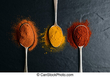 Set of three cooking spoons with spices on black background
