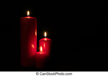 Set of three red candles burning in the dark