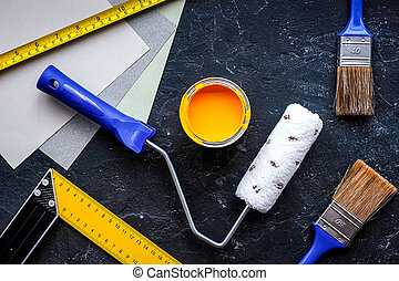 Set of tools for painting on black stone table background top view