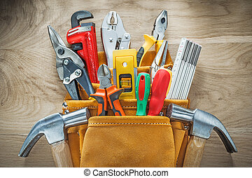 Set of tools in leather construction belt on wooden board