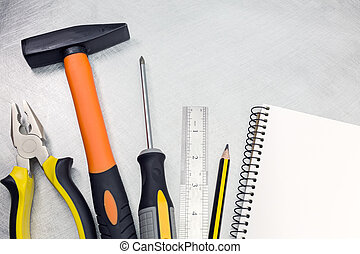 Set of tools on metal background with notepad