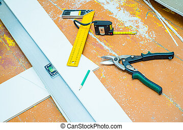 Set of tools over a wood floor with sawdust indoors