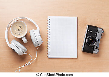 Camera, headphones, notepad and coffee cup