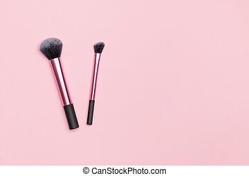Set of two different makeup brushes on a pink background. Flat lay top view