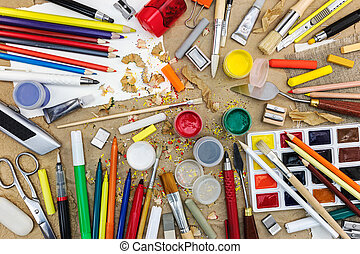 various drawing tools on brown craft paper background top view including different multicolored pencils, watercolor, paintbrushes