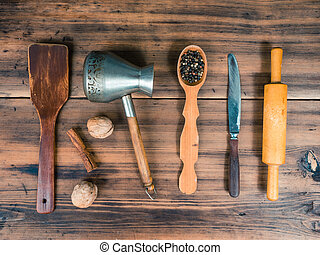 Set of various kitchen tools on old wooden table, top view. Wooden spoon, knife, rolling pin, turk for coffee, nuts and cinnamon laid out on the table, close-up view