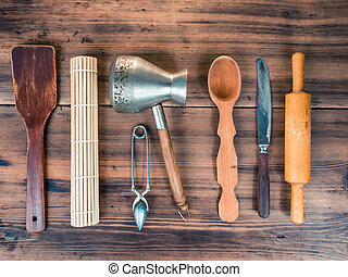 Set of various kitchen tools on old wooden table, top view. Wooden spoon, knife, rolling pin, turk for coffee custard spoon for tea laid out on the table, close-up