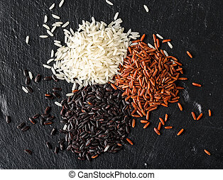 Set of various rice isolated on black background: black, basmati, and red mixed rice.