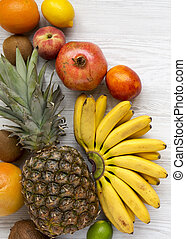 Set of various tropical fruits on a white wooden background, from above. Flat lay, overhead, top view.