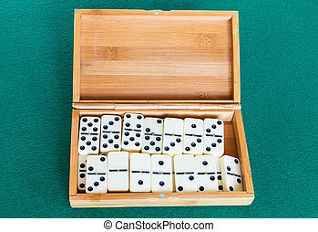 set of white dominoes tiles in bamboo box on table - set of ...