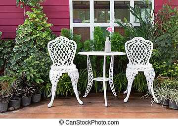 set of white furniture with table and chairs decorated in backyard