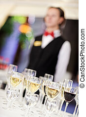 Set of wine glasses with waiter on blurred background