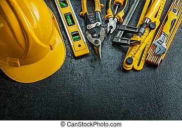 set of yellow construction tools on black background