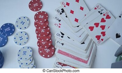 Set to playing poker with cards and chips on white...