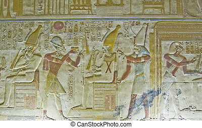 Ancient Egyptian bas relief carving showing the Pharaoh Seti I holding his flail of office before the god of the underworld Osiris with the falcon headed god Horus behind him. Abydos Temple, Egypt. Ancient carving, on public display for 2,000 years.