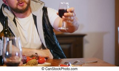 Setout. A man pours a glass of wine and offers to clink....