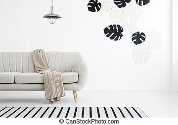 Settee in white flat interior - Monstera leaves on the wall...