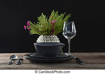 Setting a table for a dinner party with wine glass and flower vase