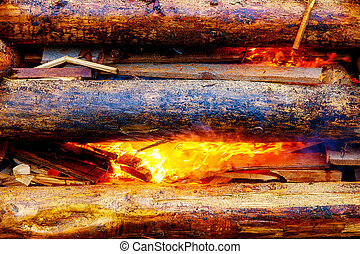 setting big bonfire made of logs on fire with torch.