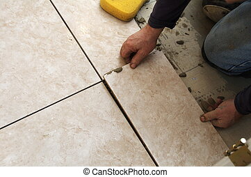 Setting Ceramic Tile - A man on his knees installing a...