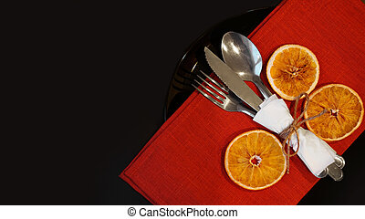 Setting for festive Christmas dinner on black table with decoration