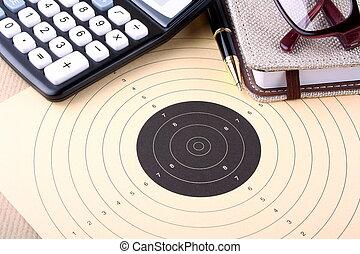 Setting goals - target, calculator, pen, notebook, glasses