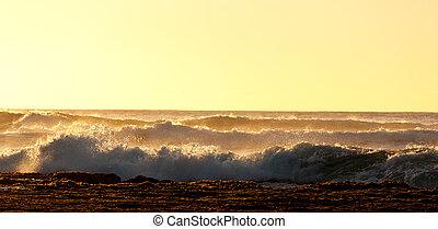 Setting sun lights crashing waves