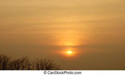 Setting Sun - Orange / yellow setting sun in clouds / haze