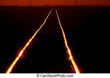 Setting sun shining on railroad tracks