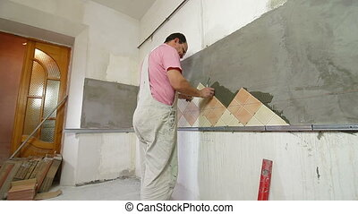 Setting Tile - Man setting tile on cement board, Side View,...