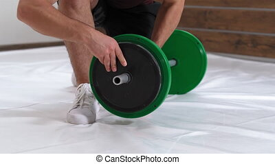 Setting up a barbell young man bow on a knee taking down a black plates, equipment for weight training concept. Sports equipment for training. Weight loss, healthy lifestyle concept. 4K footage.