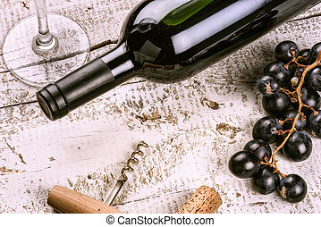Setting with bottle of red wine, grape and corks