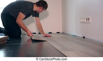 settler man laying laminate flooring in new room at home....