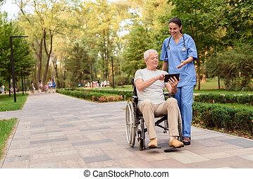 seu, antigas, tabuleta, sentando, cadeira rodas, algo, enfermeira, homem, mostra