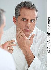 seu, aplicando, rosto, maduras, retrato, moisturizer, homem