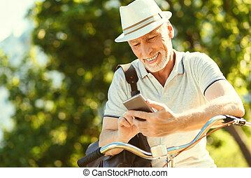 seu, encantado, smartphone, usando, homem sênior