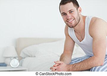 seu, sentando, homem sorridente, cama, jovem