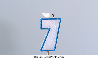 Seven birthday candle flickering and extinguishing on blue...