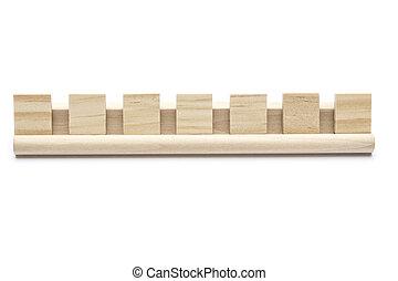 Seven blank scrabble tiles on a wooden rack, on white background