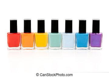 seven bottles of nail varnish on a white background