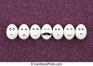 Seven eggs with different facial expressions are lying on the decorative purple sand.