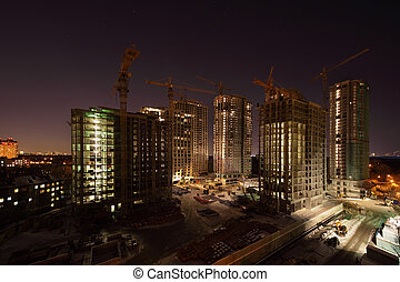 Seven high buildings under construction with cranes and illumination at dark night