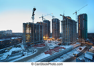 Seven high buildings under construction with cranes at day, red bricks and other building materials