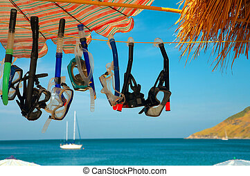 seven masks and snorkels hanging on the rope