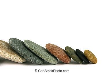 Seven pebbles line - Seven pebbles in line, over white
