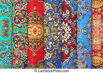 Seven varicoloured carpets lie in rouleau on each other on ...